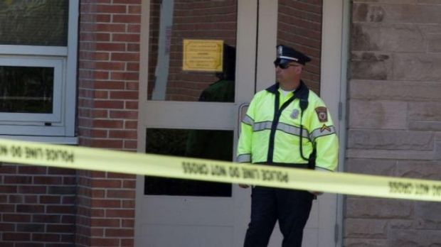 Active crime scene ... Police guard an entrance to Jonathan Law High School in Milford, Connecticut.