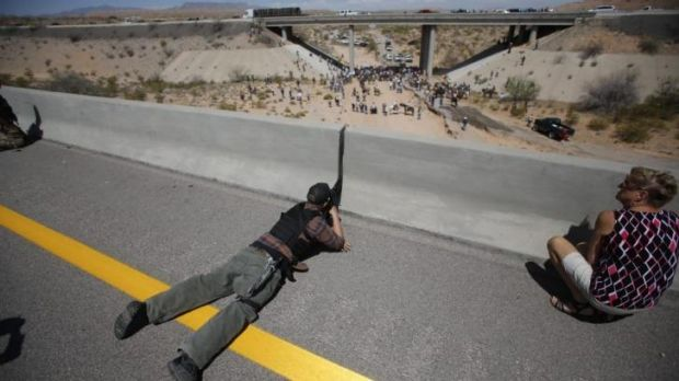 Supporter of grazing rights ... Eric Parker aims his weapon from a bridge as protesters gather by the Bureau of Land ...