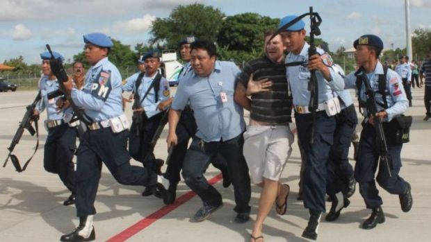 Indonesian military officers haul Matt Christopher Lockley away.