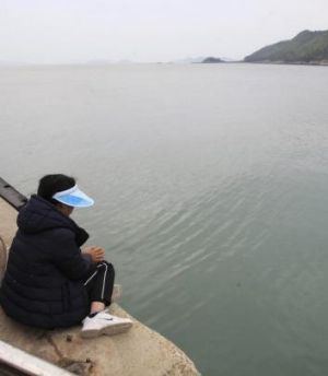 Keeping vigil: A relative awaits for news of the missing passengers.