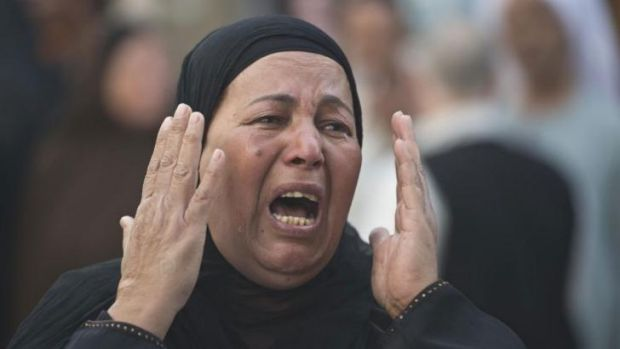 An Egyptian woman reacts outside the courtroom in Minya after Muslim Brotherhood leader Mohammed Badie and 682 other ...