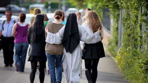 A nun comforts students after the stabbing death of one of their teachers.