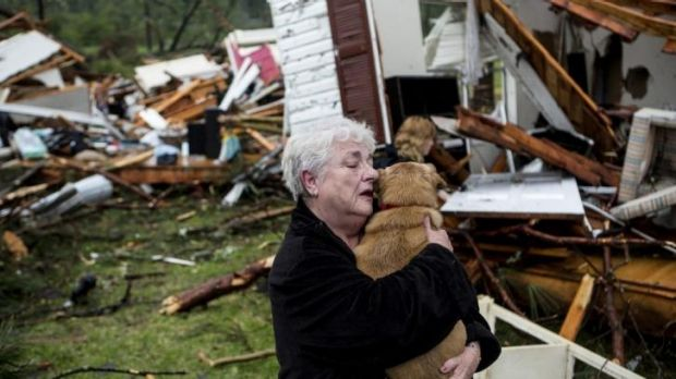 Constance Lambert embraces her dog after finding it alive on returning to her destroyed home in Tupelo.
