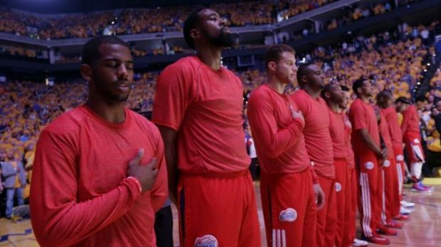 Los Angeles Clippers players listen to the national anthem wearing their warm-up jerseys inside out to protest alleged ...