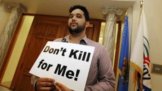 Hossein Dabiri with Oklahoma Coalition Against the Death Penalty holds a sign protesting the death penalty at the State ...
