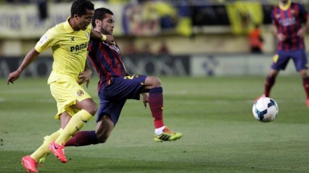 Barcelona's Dani Alves and Villarreal's Giovani Dos Santos fight for the ball during their Spanish first division soccer ...
