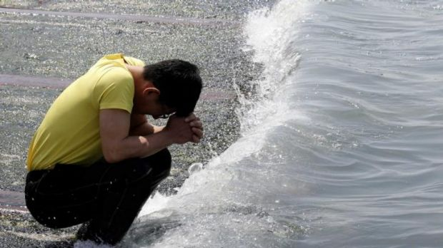 A family member of a victim of the ferry tragedy prays at a port where many families await news.
