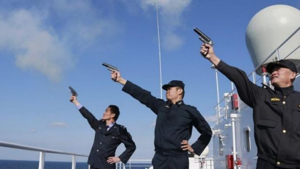 Chinese personnel fire their pistols to signal the start of a naval exercise in the East China Sea.