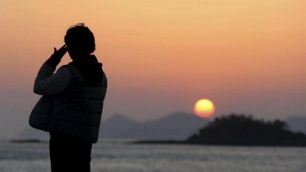 A relative of a passenger aboard the sunken Sewol ferry stands as she awaits news on her missing loved one at a port in ...