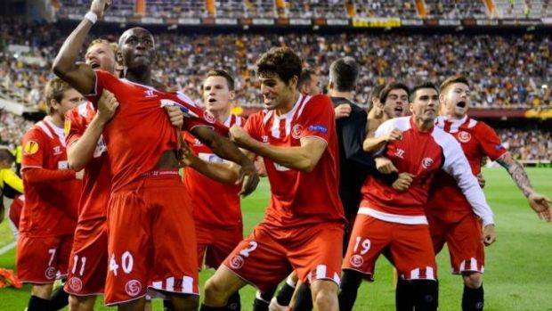 Sevilla's players celebrate their victory on away goals.