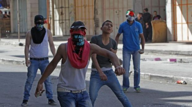 Palestinian youth throw stones at Israeli security forces in Hebron following Friday prayers on April 25.