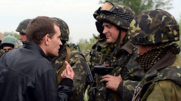 A resident speaks to Ukrainian soldiers in the village of Andreevka.