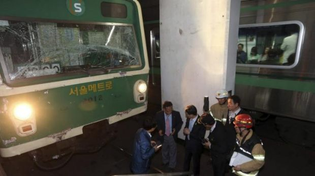 Investigators inspect the site where two subway trains collided in Seoul.