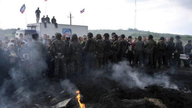 Staunch opposition ... Ukrainian soldiers (foreground) face Pro-Russia separatists blocking the road into Slavyansk.