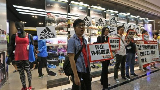 Protesters hold banners and placards during a protest outside an Adidas shop at a shopping mall during Labour Day in ...