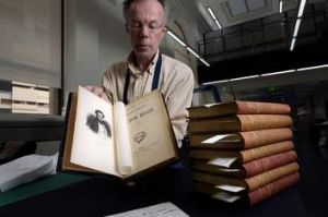 Conservator Ian Cox with volumes of <i>Les Miserables</i>.