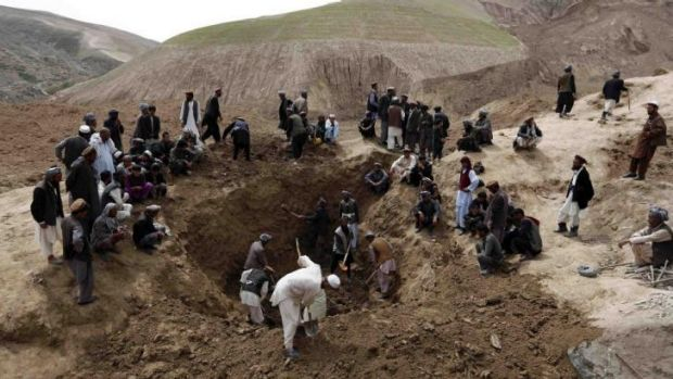 Villagers gather at the site of the landslide in Badakhstan province on Sunday.