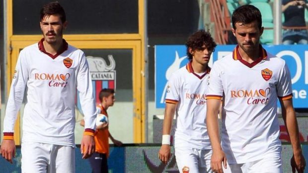 Dejected Roma players  Alessio Romagnoli, Dodo and Miralem Pjanic leave the pitch after their loss to Sicilian club Catania.