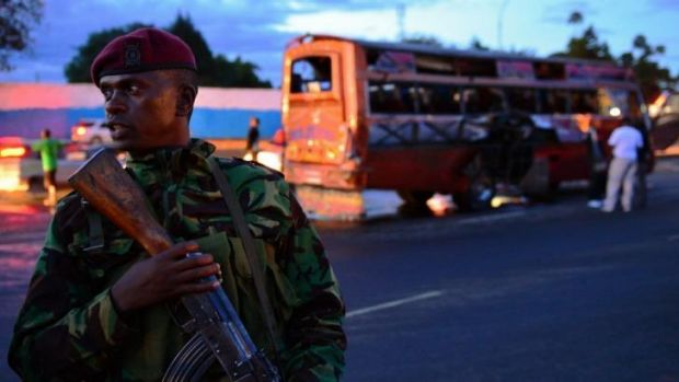 Bomb scene: a Kenyan policeman stands in front of a wrecked bus in Nairobi.