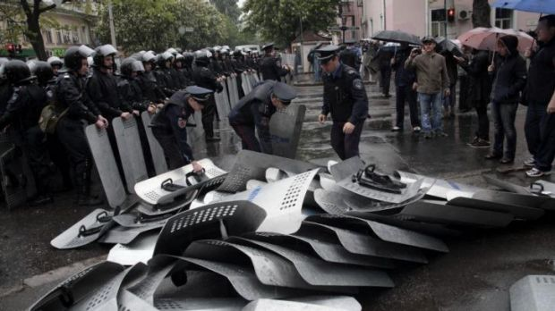 Ukrainian police work to remove riot shields left on the ground by their colleagues outside police headquarters in ...