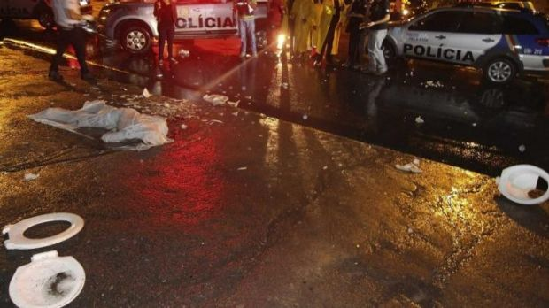 The wrapped body of Paulo Ricardo Silva, 26, a soccer fan who was killed in clashes between fans, lies on a street as ...