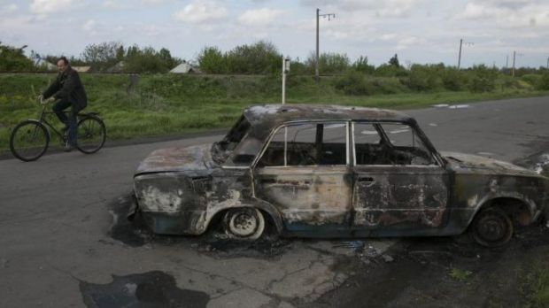 A cyclist rides by a burnt car at a crossroad that was the centre of fierce fighting between the Ukrainian army and ...