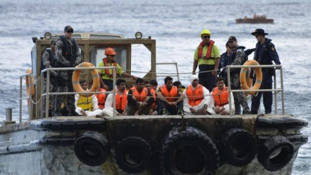 Australian customs officials and navy personnel escort asylum-seekers onto Christmas Island in August, 2013.