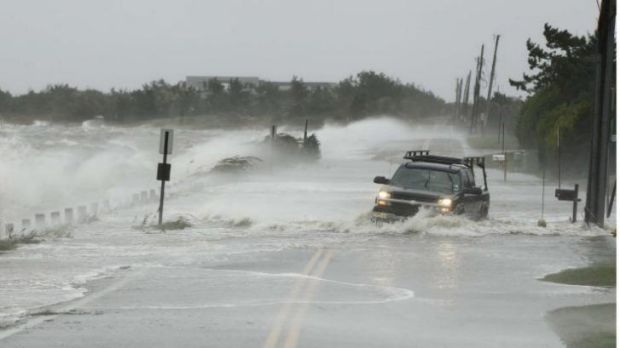 A truck drives through storm surge flooded road during Superstorm Sandy on October 29, 2012. The global warming report ...
