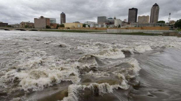 Extreme conditions ... Water splashes over the Centre Street Dam in the swollen Des Moines River in downtown Des Moines, ...