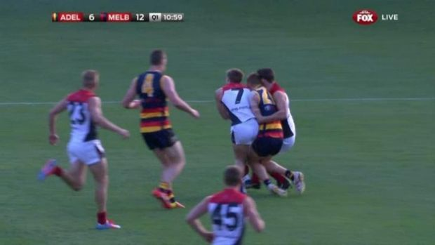 Melbourne's Jack Viney (number 7) collides with Crows Tom Lynch and Alex Georgiou in round seven.