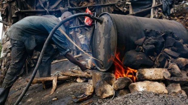 A man stoking the fire of a 'chang'aa' distillery in the Mathare slum of Nairobi. The illegal brew is now thought ...