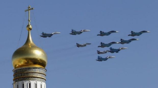 Flexing its muscle ... Russian military jets fly above the Kremlin, with the Ivan the Great Bell Tower seen in the ...