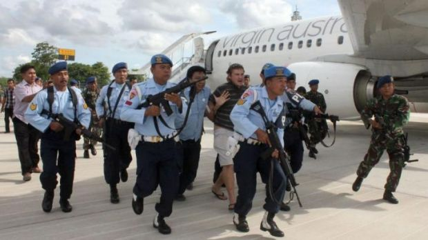 Matt Lockley (centre back) is arrested by Indonesian Air Force soldiers after landing on the Virgin Australia 737-800 ...