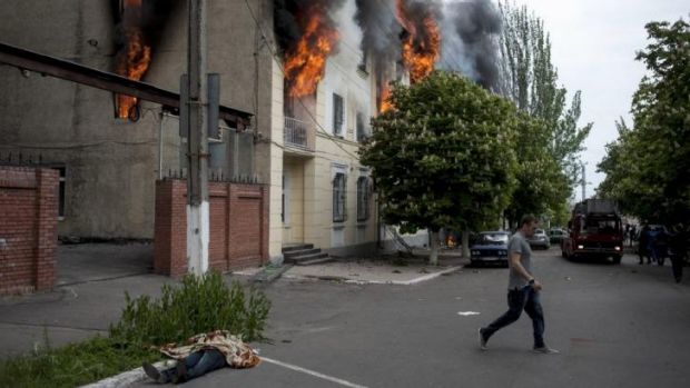 The body of a police officer, left, lies outside a police station that burns in Mariupol, eastern Ukraine. A clash ...