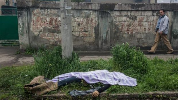 The body of a man killed in the clash between Ukraine and pro-Russian forces lies along the street near a police station ...
