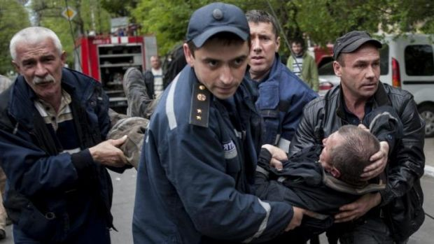 Police and citizens carry a firefighter injured during an attack on a police station in Mariupol, eastern Ukraine.