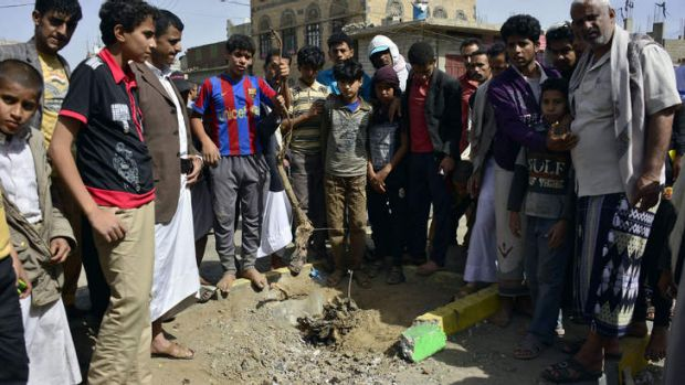 Yemenis gather at the site of a bomb explosion that targeted an army troop vehicle.
