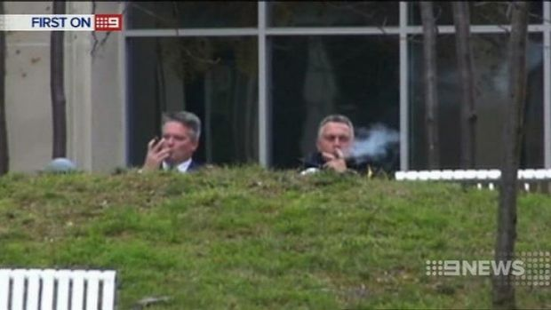 Caught on camera: Mathias Cormann and Joe Hockey kick back with a cigar.