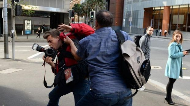 Waiting in the wings: Bruce Wilson attacks a photographer outside the hearing.