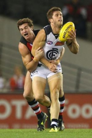 Marc Murphy handballs while being tackled by Lenny Hayes.
