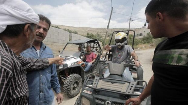 Palestinian villagers block the road in front of armed Israeli settlers attempting to enter the village of Burin from ...