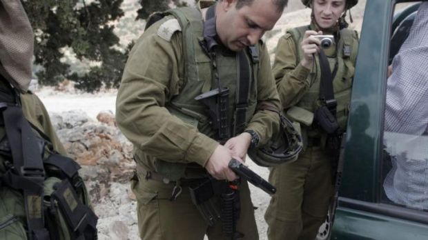 Israeli soldiers inspect pistols taken from Israeli settlers who entered the West Bank village of Burin on Monday.