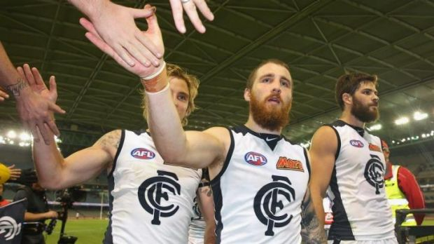Carlton's Dennis Armfield and Zach Tuohy high-five fans as they leave the ground on Monday night after defeating the Saints.