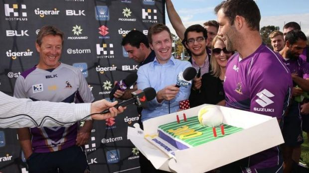 Cameron Smith presents Craig Bellamy with a cake to mark his 300th game as Storm coach.