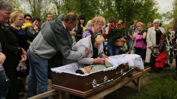 The mother of 39-year-old miner Vadim Hudich embraces her son  during his funeral.
