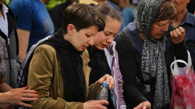 The wife (left) and daughter (2nd from left) of Vadim Hudich, mourn at his funeral.