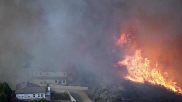 A wildfire approaches homes in San Marcos, California, on Wednesday.