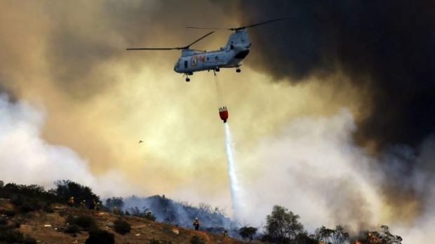 A US military helicopter drops water on a fire in San Marcos.