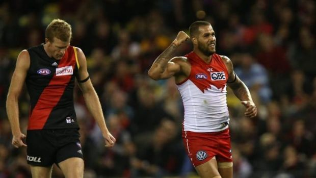 Lance Franklin shakes his fist in triumph after kicking a goal as Dustin Fletcher watches.