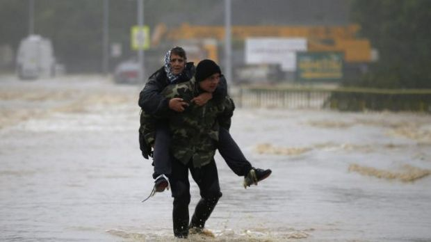 A man carries a woman through a flooded street in the town of Obrenovac, east from Belgrade.